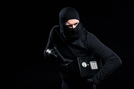 Ladrón en pasamontañas con pistola y caja fuerte cerrada Foto de archivo