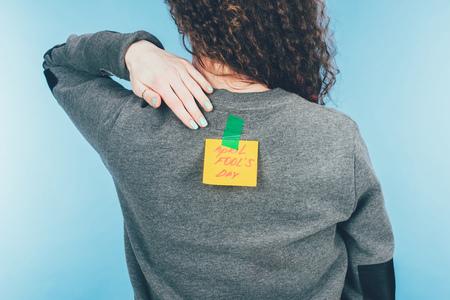 Rückansicht der Frau mit Hinweis auf Klebeband mit Aprilscherztag-Schriftzug auf der Rückseite, Aprilscherztag-Konzept