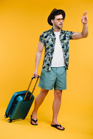 Young man with suitcase looking away and waving hand isolated on yellow background