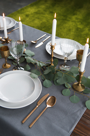 Close up view of rustic table setting with eucalyptus, vintage tarnished cutlery, candles in candle holders and empty plates Imagens