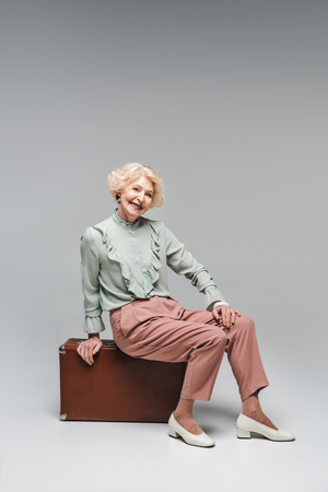 Beautiful senior woman sitting on vintage suitcase on grey background Stock Photo