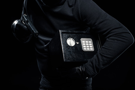 Close-up view of gun and locked safe in hands of thief