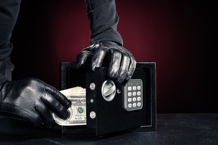 Close-up view of robber with stealing dollar banknotes from safe Stock Photo