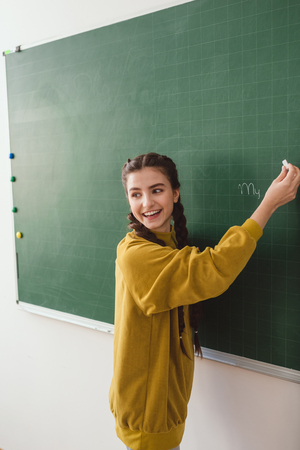 Smiling high school female student writing on chalk board Stock fotó