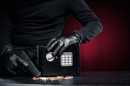 Close-up view of robber with gun taking bitcoin from safe box Stock Photo