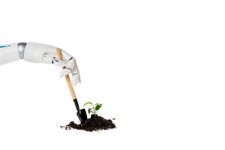 Cropped shot of robot shoveling heap of ground with small plant isolated on white background Stock Photo