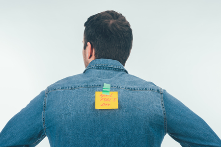 Back view of man with note on sticky tape with April fools day lettering on back, April fools day holiday concept
