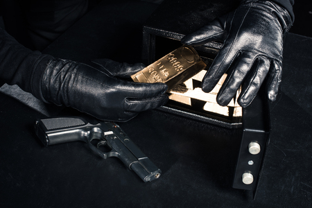 Close-up view of robber with gun taking gold bars from safe box