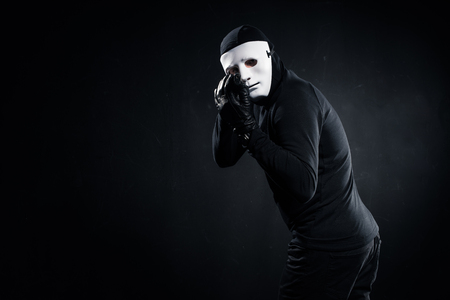 Male robber in mask aiming with gun on black background