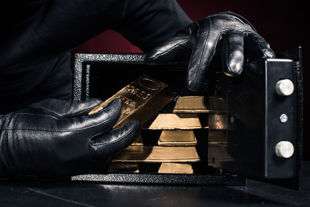 Cropped view of thief stealing gold ingots from safe box
