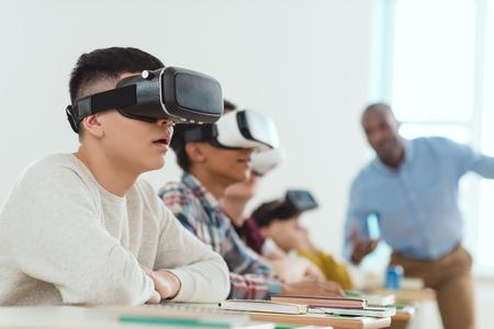 Vista laterale di scolari multiculturali che utilizzano cuffie per realtà virtuale e insegnante parlante in piedi dietro