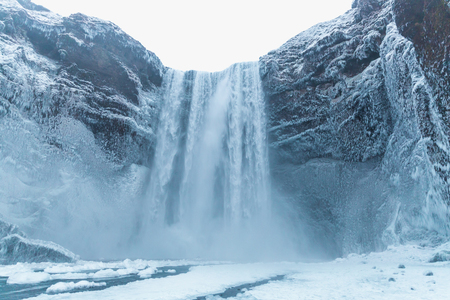 Beautiful view of scenic Skgafoss waterfall and snow-covered rocks in Iceland 写真素材