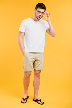Handsome young man in shorts and flip-flops adjusting sunglasses and looking at camera isolated on yellow background