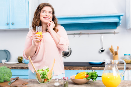 Portrait of overweight smiling woman with glass of juice in kitchen at home Imagens