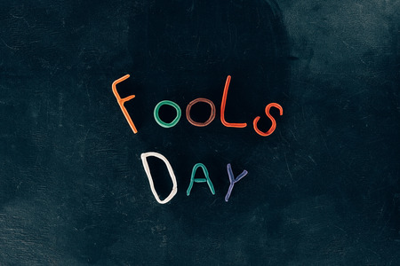 Top view of fools day lettering made of plasticine on black surface