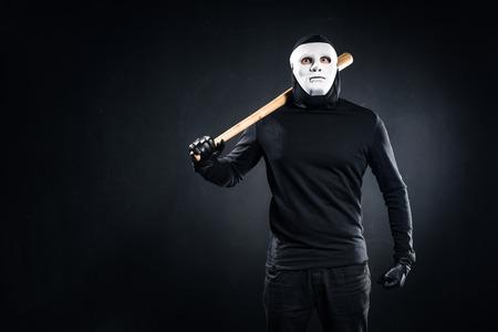 Burglar in mask and balaclava holding baseball bat