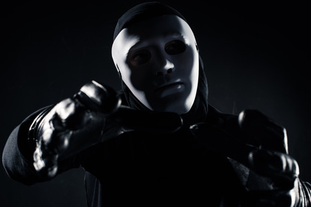 Man in mask reaching to the camera with his hands