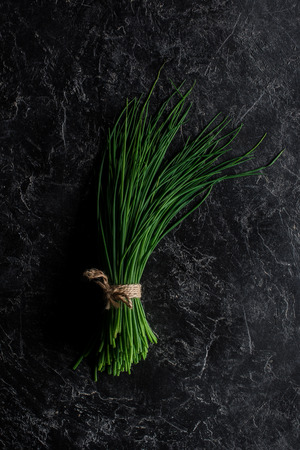 Top view of bunch of chives on concrete table, healthy eating concept