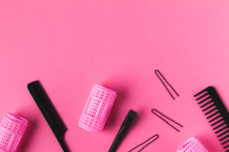 Top view of curlers, combs and hairdressing tools, on pink background