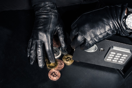 Cropped view of robber stealing bitcoin from safe Stock Photo