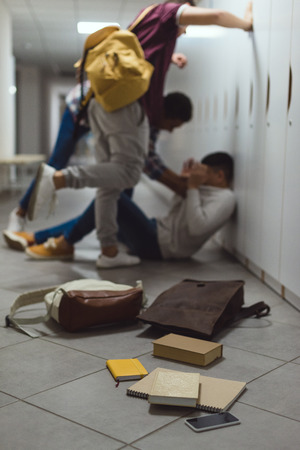 Blurred shot of schoolboy being bullied by classmates in school corridor under lockers with spilled books from backpack on floor Stock Photo
