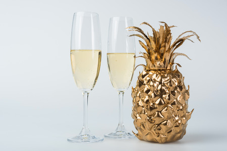 Glasses of champagne and golden pineapple on white background