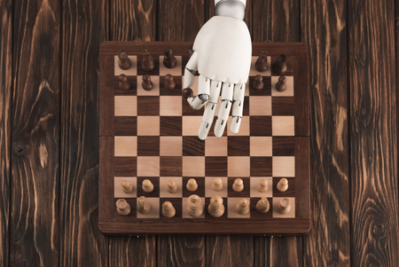 Cropped shot of robot playing chess on wooden surface