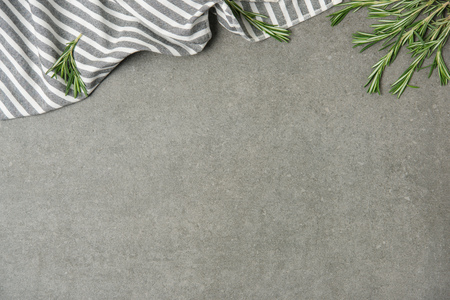 Flat lay with rosemary twigs and striped linen on grey concrete surface