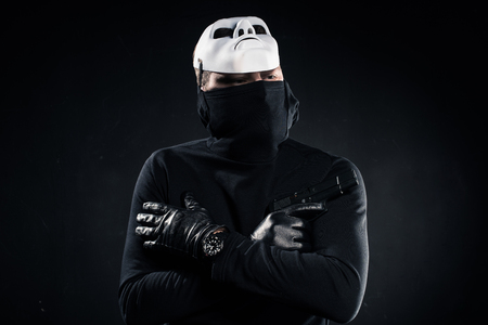 Thief in black balaclava and white mask holding gun in folded arms on black background
