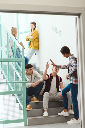 Group of high school students spending time on stairs at school together on break