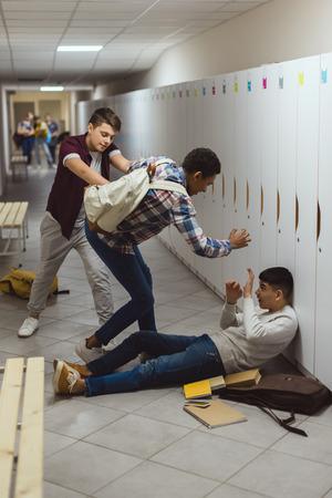 Colegiales asiáticos y afroamericanos siendo intimidados en el pasillo de la escuela por su compañero de clase