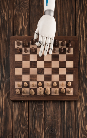 Cropped shot of robot playing chess on wooden tabletop Stok Fotoğraf