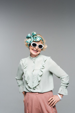Happy senior woman in stylish headband and sunglasses isolated on grey background