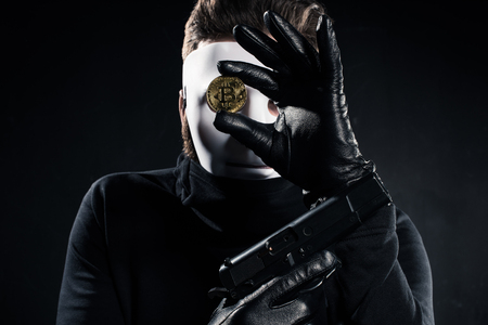 Thief in white mask holding gun and golden bitcoin Stock Photo