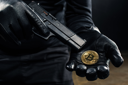 Close-up view of gun and bitcoin in hands of thief Stock Photo