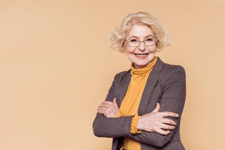 Smiling fashionable senior woman in eyeglasses posing isolated on beige background Stock Photo
