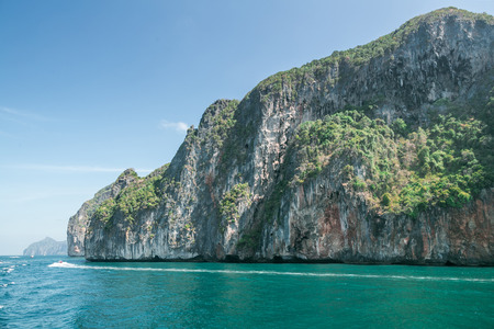 Scenic view of rocky formations covered with green plants, blue sky and ocean in Phi Phi islands