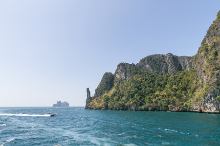 Scenic view of rocky formations covered with green plants, blue sky and ocean, Phi Phi islands Stok Fotoğraf - 110950496