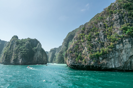 Scenic view of rocky formations covered with green plants, blue sky and ocean, Phi Phi islands Stok Fotoğraf