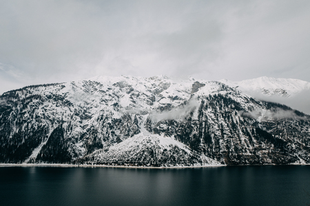 Calm alpine lake and snow-covered mountains at cloudy day, Mayrhofen, Austria 写真素材