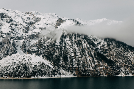 Beautiful snow-covered rocky mountains and calm mountain lake at winter, Austria 写真素材