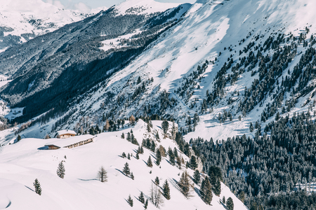 Aerial view of traditional wooden houses in majestic snow-covered winter mountains, Mayrhofen ski area, Austria