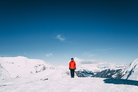 Young man smiling at camera while standing in snow-covered mountains in Mayrhofen ski area, Austria 写真素材