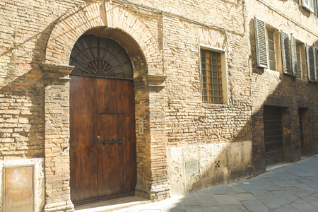 Old door in brick building facade in Sienna Фото со стока
