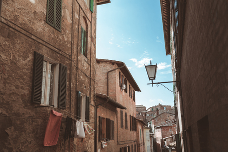 Narrow street with arch in historical quarter of Sienna
