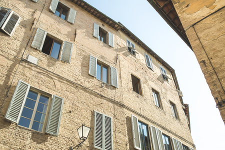 Brick building facade in historical quarter of Sienna
