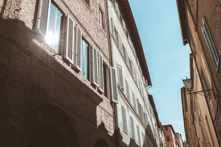Sun reflecting in window of old building in Sienna