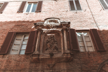 Classical statue on building facade in Sienna
