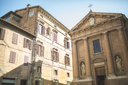Church of Saint Christopher with statues on facade in Sienna, Italy Фото со стока