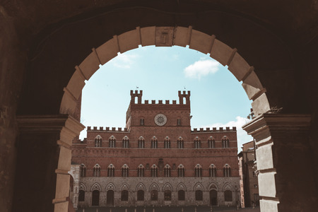 View of Piazza Del Campo through archway in Sienna